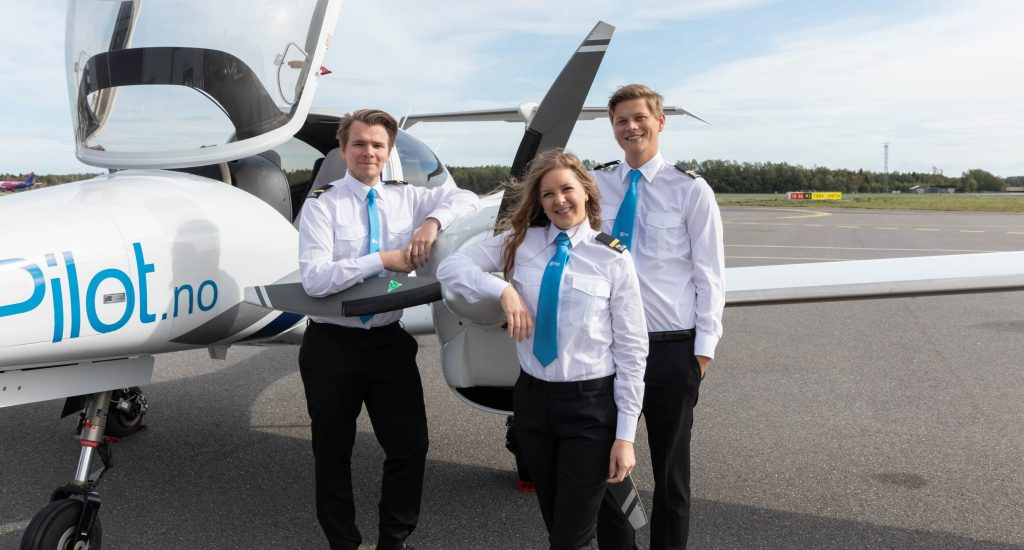 Two boys and a girl in uniforms standing by the propeller of a Diamond DA42 outside Pilot Flight Academy