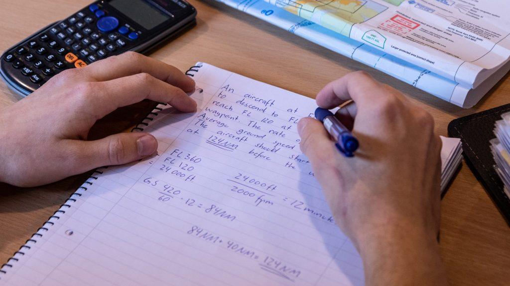 Student Hjerpsted gjør et regnestykke på papir