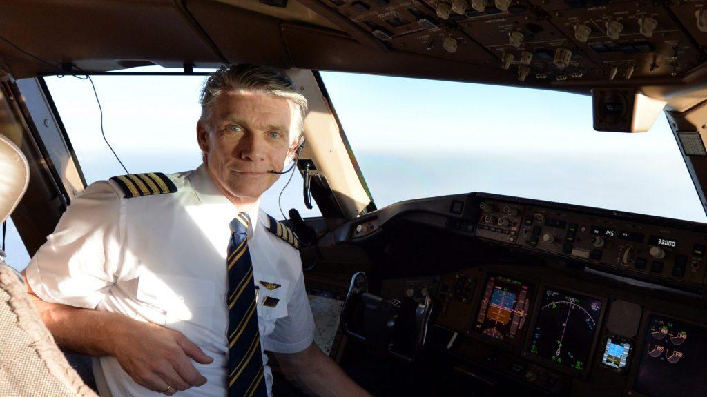 Kaptein Rosenlund sitter i cockpit på et passasjerfly og ser mot kamera